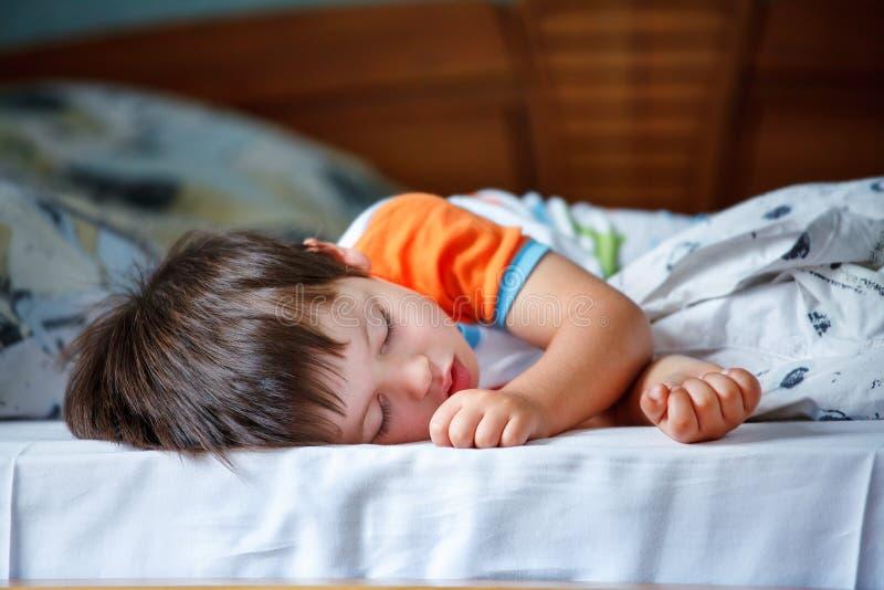 Rapaz pequeno bonito que dorme em uma cama fotografia de stock
