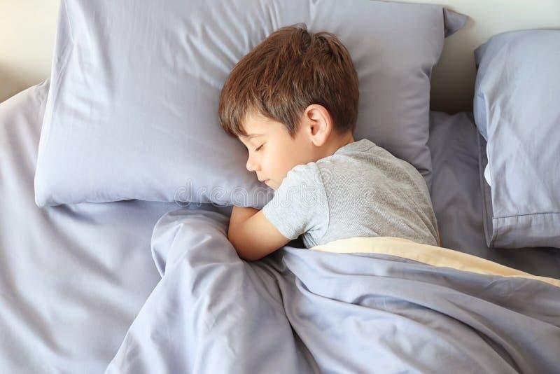 Rapaz pequeno bonito que dorme na cama imagem de stock