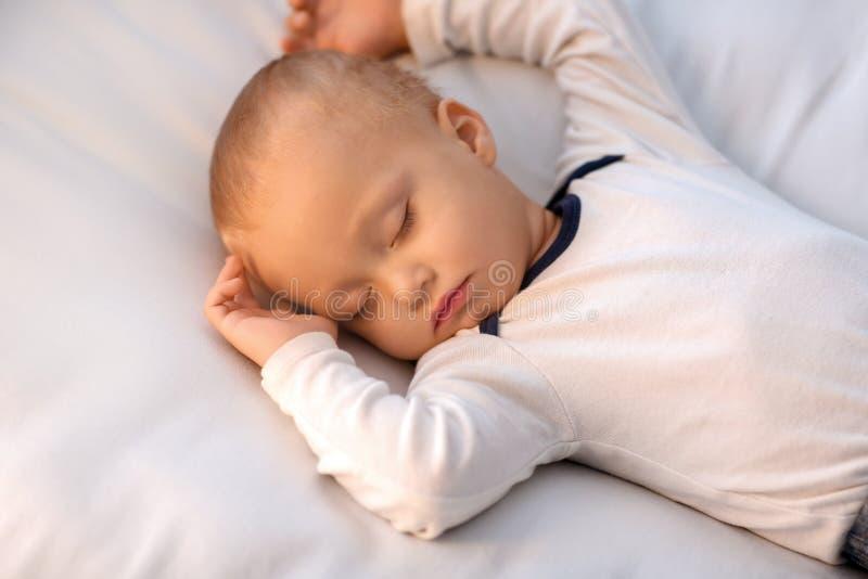 Rapaz pequeno bonito que dorme na cama fotos de stock royalty free