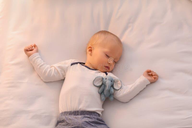 Rapaz pequeno bonito que dorme na cama fotos de stock