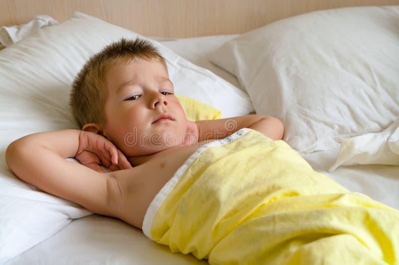 Rapaz pequeno bonito que encontra-se na cama fotografia de stock