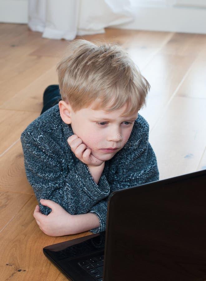 Rapaz pequeno bonito que encontra-se no assoalho usando um portátil fotos de stock