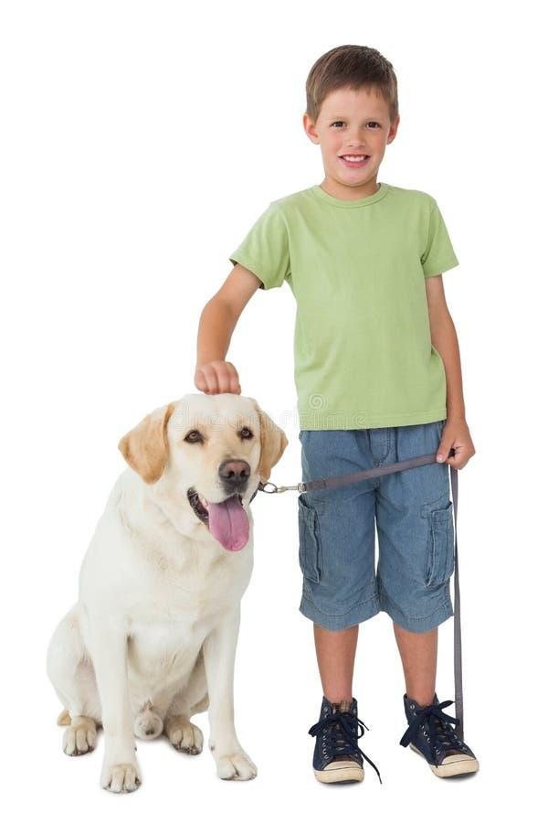 Rapaz pequeno bonito que está com seu cão de Labrador que sorri na câmera fotografia de stock