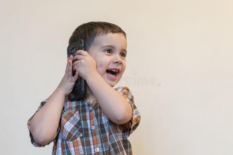 Rapaz pequeno bonito que fala pelo telefone celular no fundo claro Posi??o feliz do rapaz pequeno e fala no smartphone em casa imagens de stock royalty free