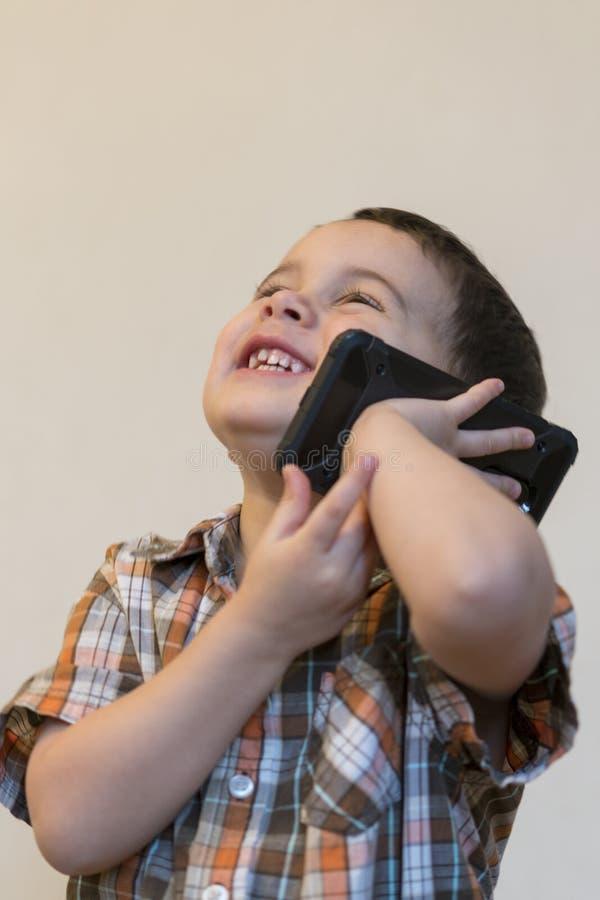 Rapaz pequeno bonito que fala pelo telefone celular no fundo claro Posi??o feliz do rapaz pequeno e fala no smartphone em casa imagens de stock