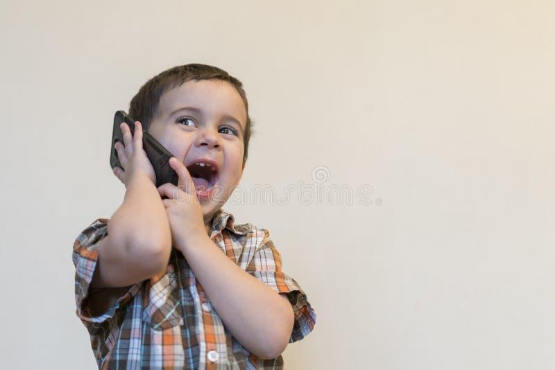 Rapaz pequeno bonito que fala pelo telefone celular no fundo claro Posi??o feliz do rapaz pequeno e fala no smartphone em casa foto de stock royalty free