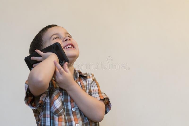 Rapaz pequeno bonito que fala pelo telefone celular no fundo claro Posi??o feliz do rapaz pequeno e fala no smartphone em casa imagem de stock royalty free