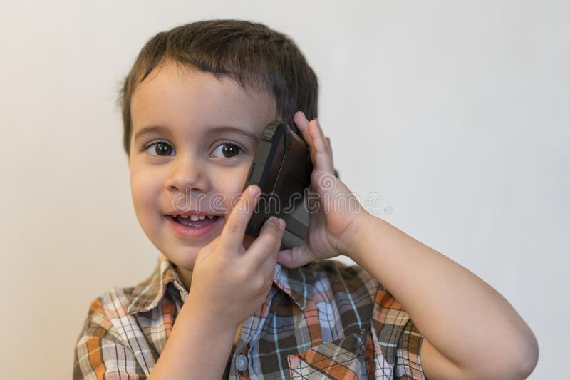 Rapaz pequeno bonito que fala pelo telefone celular no fundo claro Posi??o feliz do rapaz pequeno e fala no smartphone em casa fotos de stock royalty free