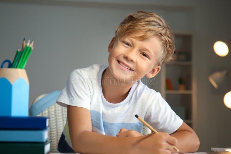 Rapaz pequeno bonito que faz suas lições em casa imagens de stock royalty free