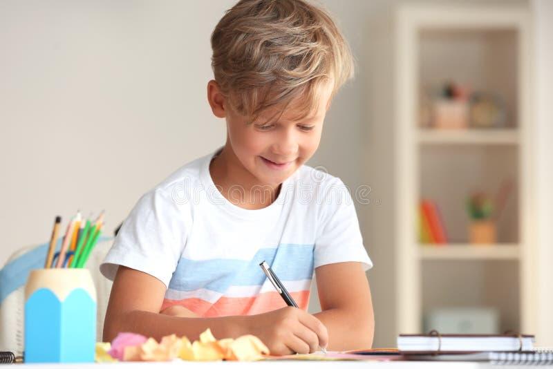 Rapaz pequeno bonito que faz suas lições em casa imagem de stock