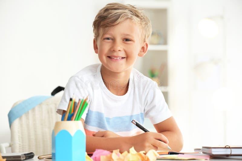 Rapaz pequeno bonito que faz suas lições em casa foto de stock