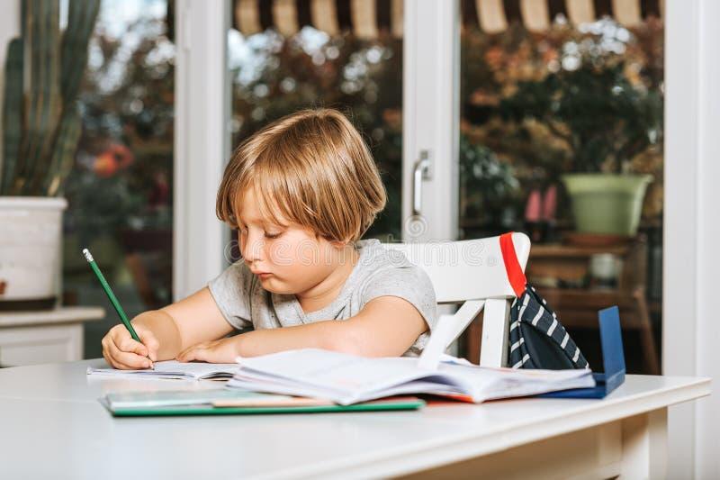 Rapaz pequeno bonito que faz trabalhos de casa para a escola imagem de stock