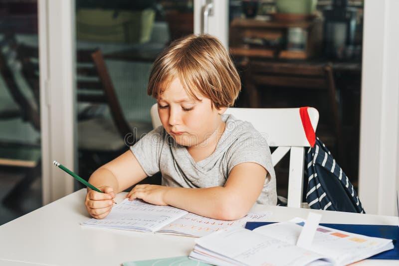 Rapaz pequeno bonito que faz trabalhos de casa para a escola imagens de stock royalty free
