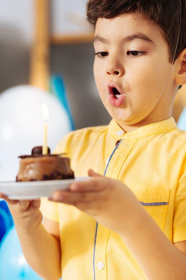 Rapaz pequeno bonito que funde para fora a vela em seu bolo de aniversário fotografia de stock