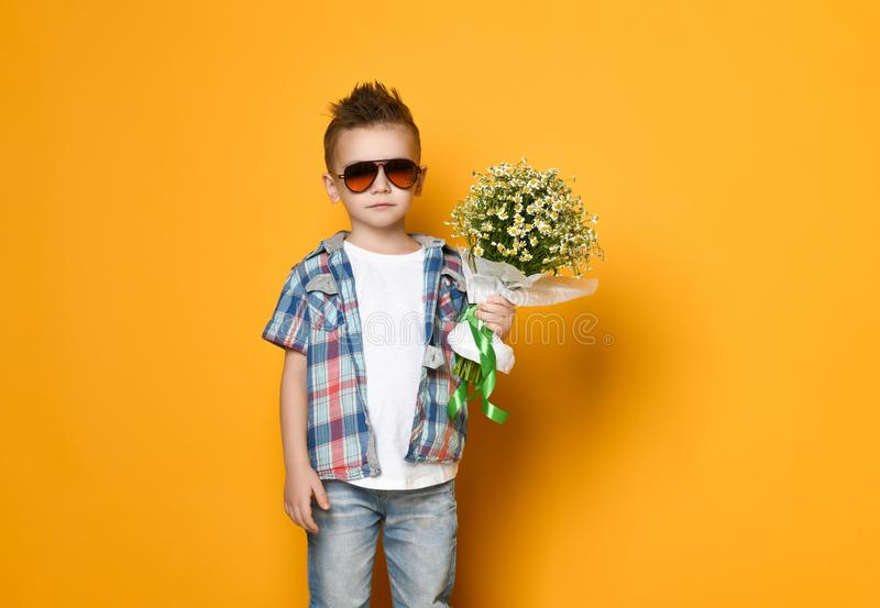 Rapaz pequeno bonito que guarda um ramalhete das flores fotografia de stock