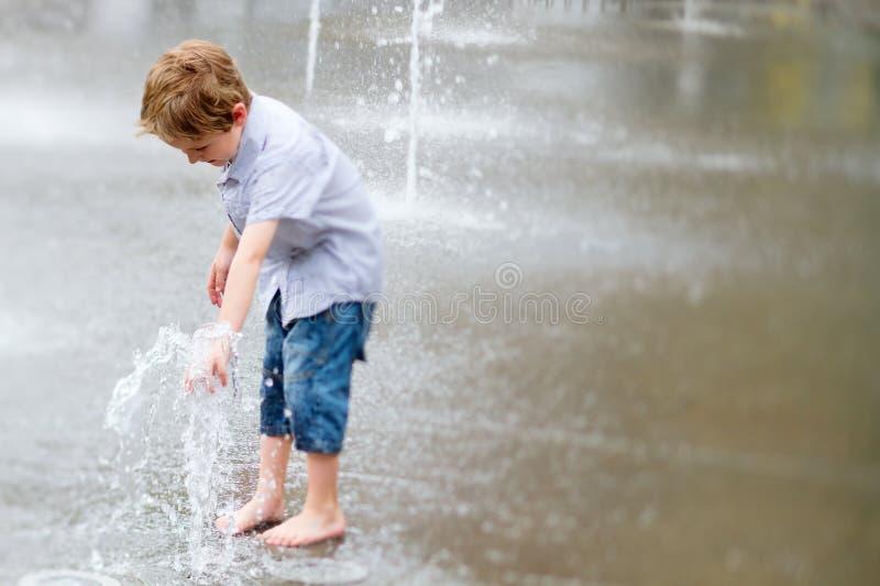 Rapaz pequeno bonito que joga com água ao ar livre imagem de stock