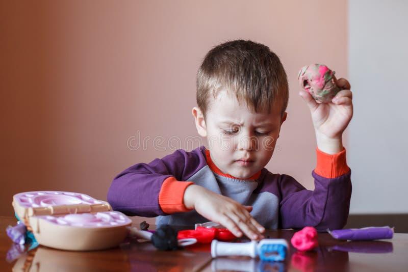 Rapaz pequeno bonito que joga com plasticine multicolorido Menino que joga com as ferramentas dentais dos brinquedos Express?o fa imagens de stock