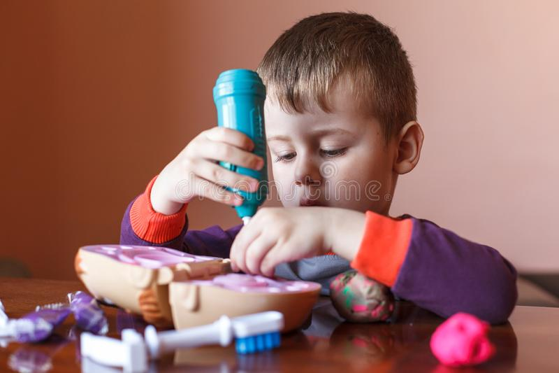 Rapaz pequeno bonito que joga com plasticine multicolorido Menino que joga com as ferramentas dentais dos brinquedos Express?o fa foto de stock royalty free