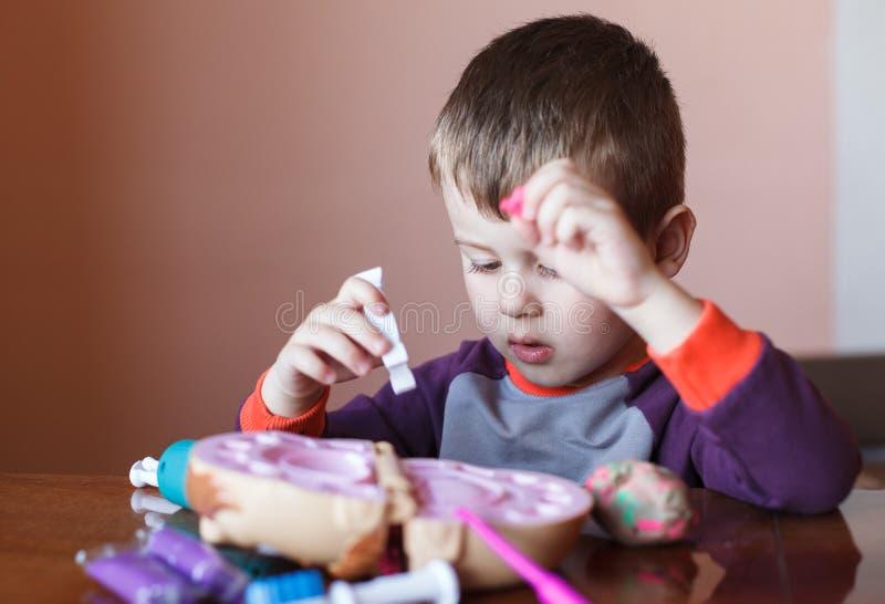 Rapaz pequeno bonito que joga com plasticine multicolorido Menino que joga com as ferramentas dentais dos brinquedos Express?o fa fotografia de stock royalty free