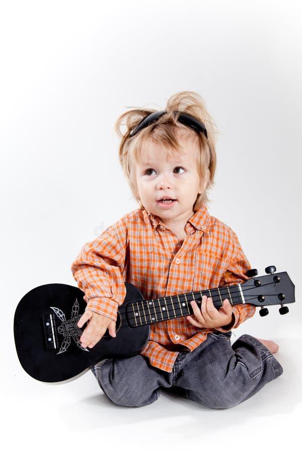 Rapaz pequeno bonito que joga a guitarra do ukulele fotos de stock