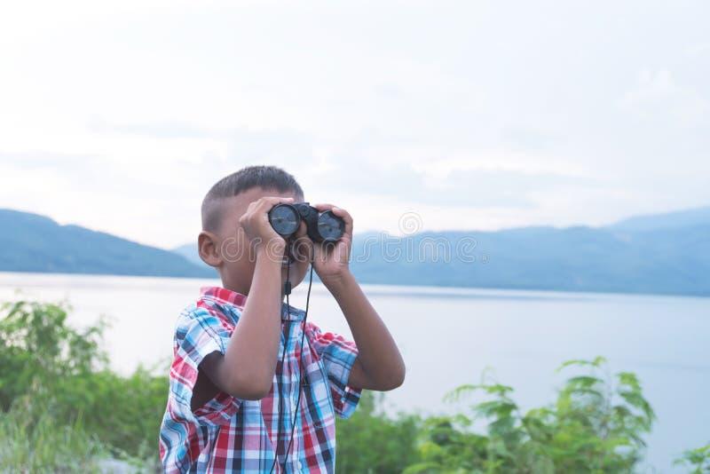 Rapaz pequeno bonito que olha com binocular fotografia de stock royalty free