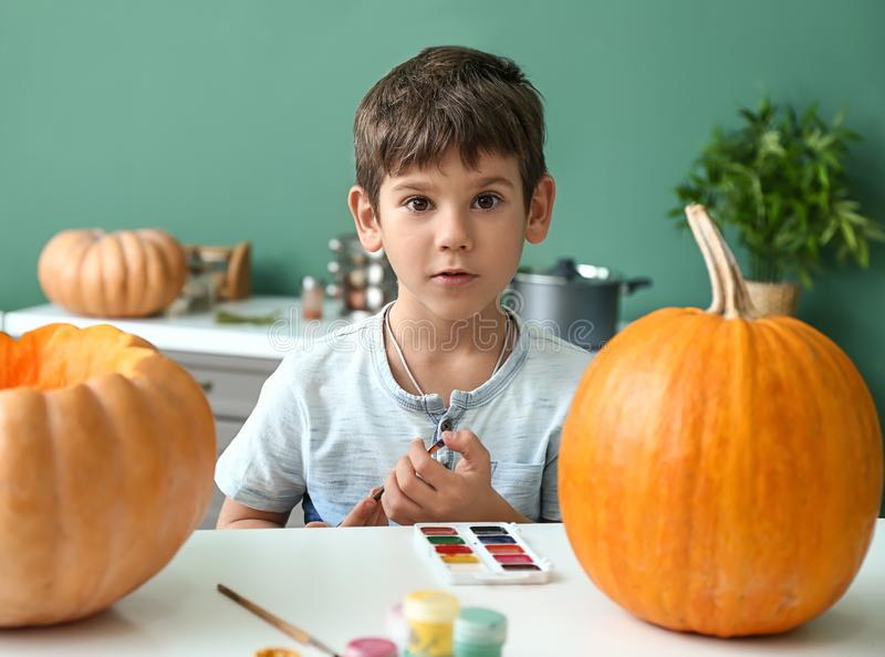 Rapaz pequeno bonito que prepara abóboras para Dia das Bruxas em casa imagens de stock