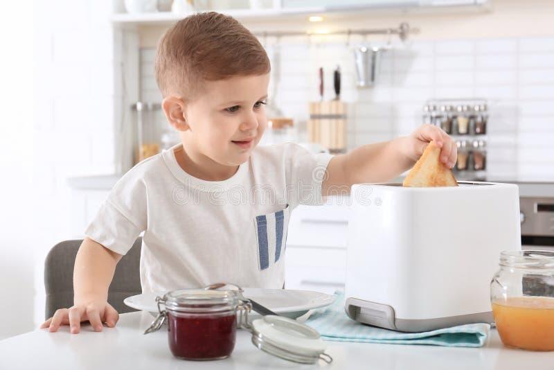 Rapaz pequeno bonito que prepara o brinde com doce doce imagem de stock royalty free