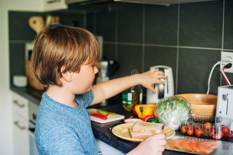 Rapaz pequeno bonito que prepara o sanduíche dos salmões com ingredientes frescos foto de stock royalty free