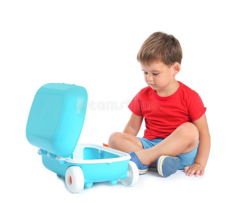 Rapaz pequeno bonito que senta-se com mala de viagem azul imagem de stock royalty free