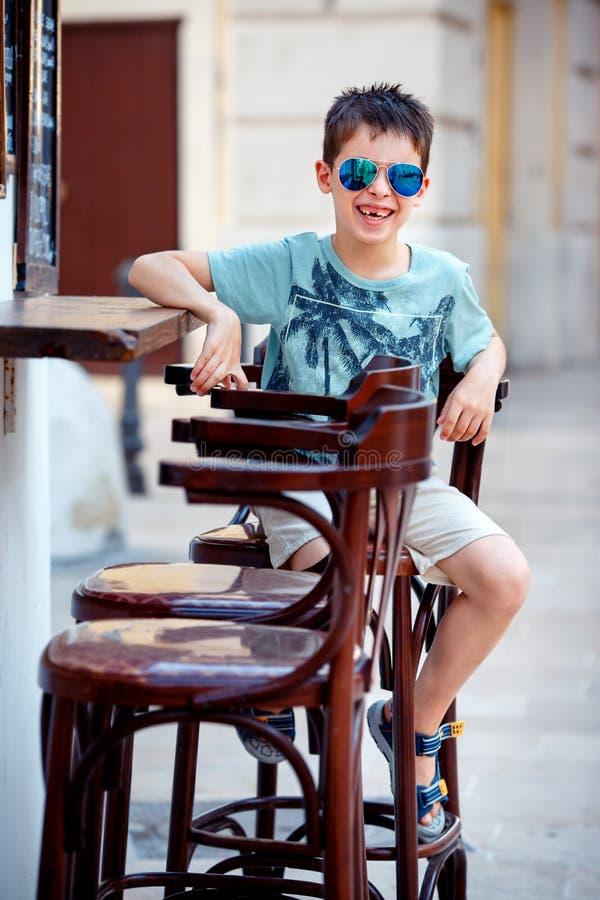 Rapaz pequeno bonito que senta-se em uma cadeira no café exterior foto de stock