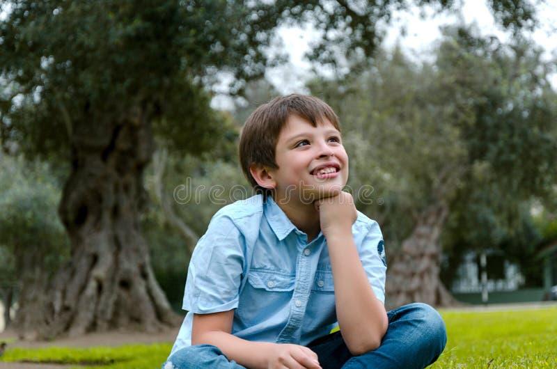 Rapaz pequeno bonito que senta-se no pensamento de sorriso do parque foto de stock royalty free