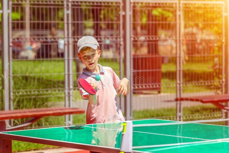 Rapaz pequeno bonito que tem o divertimento que joga o t?nis de mesa na terra de esporte do parque imagens de stock