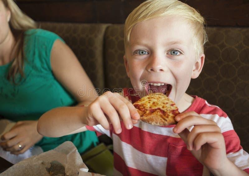 Rapaz pequeno bonito que toma uma mordida grande da pizza de queijo em um restaurante imagem de stock royalty free