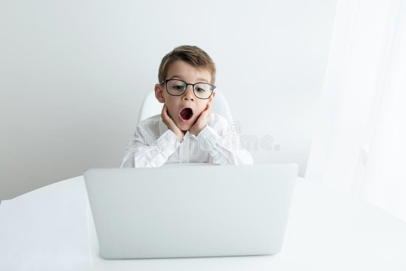 Rapaz pequeno bonito que usa o port?til ao fazer trabalhos de casa contra o fundo branco imagens de stock royalty free