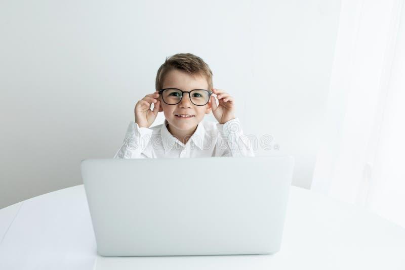 Rapaz pequeno bonito que usa o port?til ao fazer trabalhos de casa contra o fundo branco imagens de stock