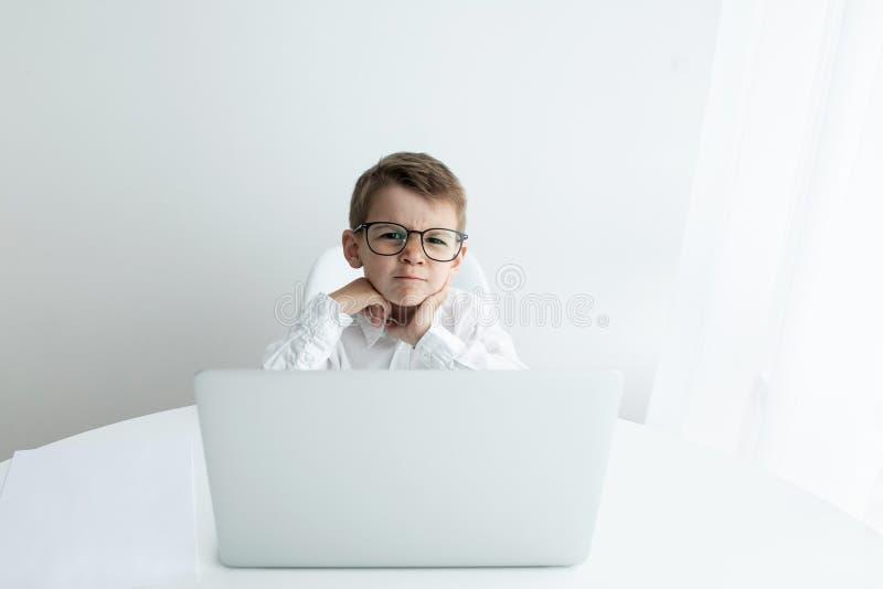 Rapaz pequeno bonito que usa o port?til ao fazer trabalhos de casa contra o fundo branco fotos de stock
