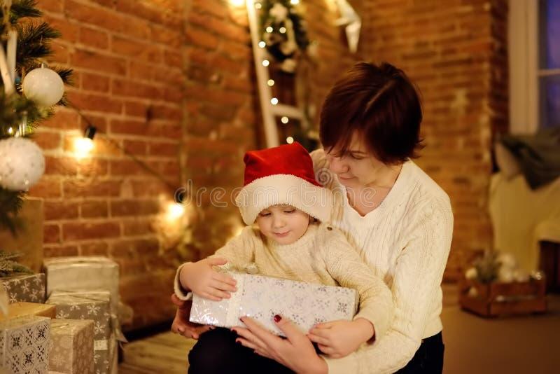 Rapaz pequeno bonito que veste o chapéu de Santa e a sua mãe ou avó na Noite de Natal fotografia de stock