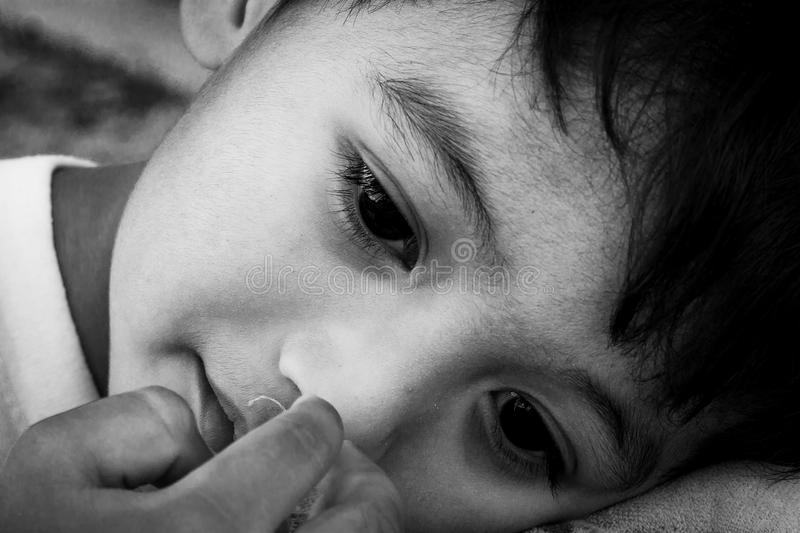 Rapaz pequeno bonito triste, tom preto e branco da cara foto de stock