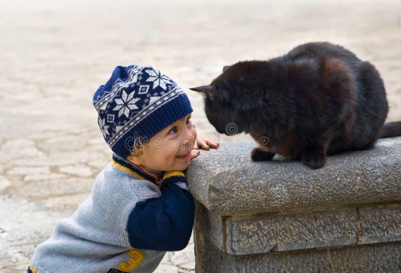 Rapaz pequeno Charming que joga com um gato preto foto de stock