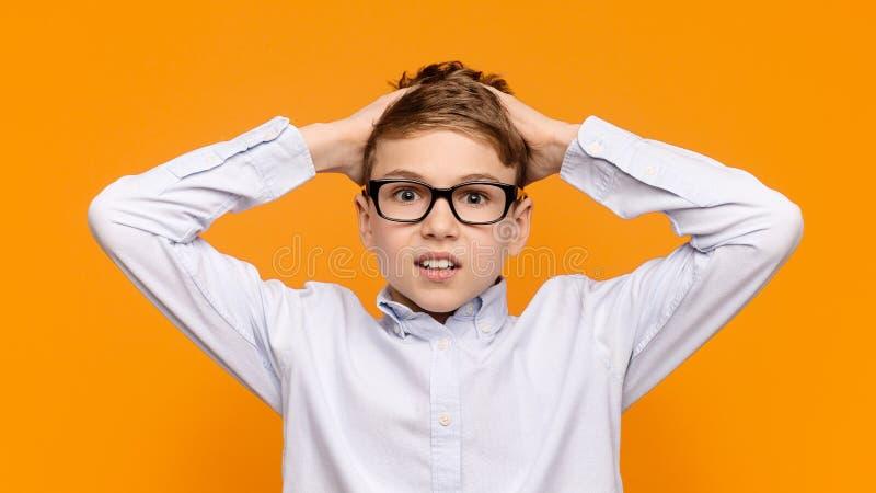Rapaz pequeno chocado que incomoda, tocando em seu cabelo fotos de stock