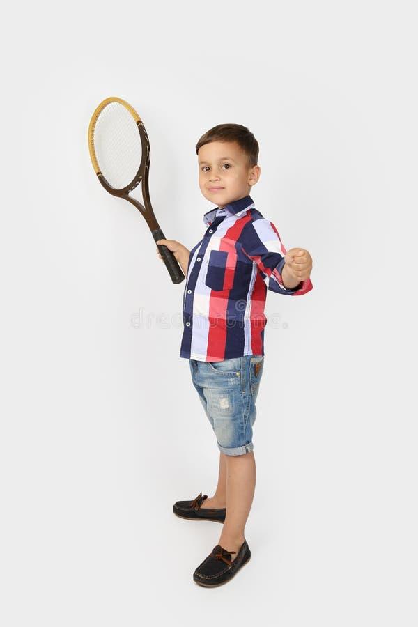 Rapaz pequeno com as raquetes de tênis no cinza imagem de stock