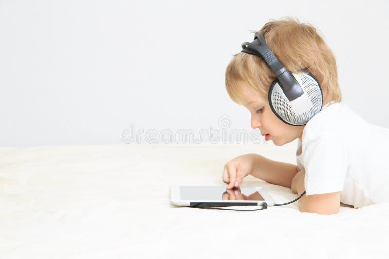 Rapaz pequeno com auriculares usando a almofada de toque foto de stock royalty free