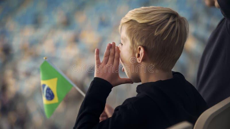 Rapaz pequeno com bandeira brasileira que chanting no estádio a favor da equipe de futebol fotografia de stock