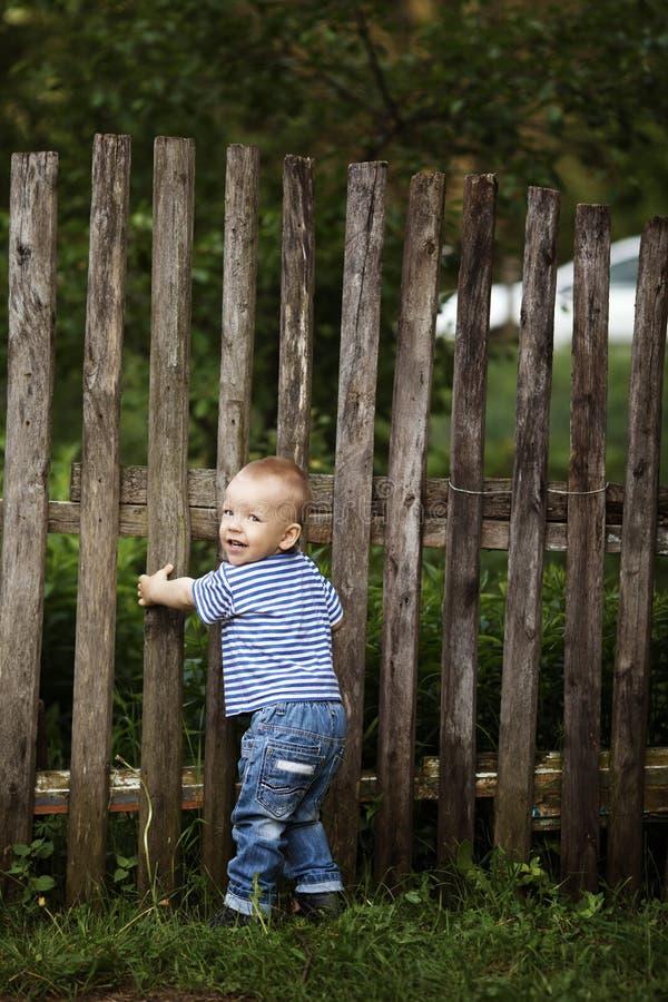 Rapaz pequeno com cerca fora imagens de stock royalty free