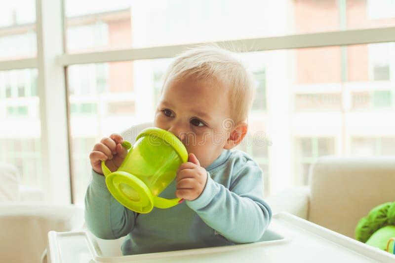 Rapaz pequeno com copo do bebê imagens de stock royalty free
