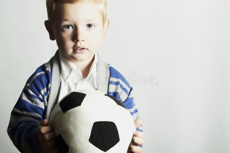 Rapaz pequeno com a criança do futebol ball.stylish. crianças da forma foto de stock royalty free
