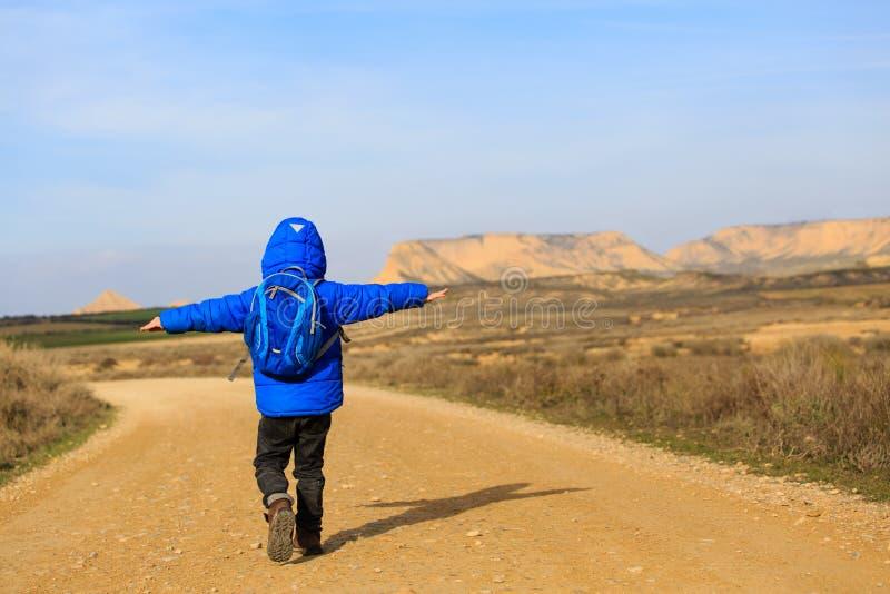 Rapaz pequeno com curso da trouxa na estrada às montanhas cênicos foto de stock