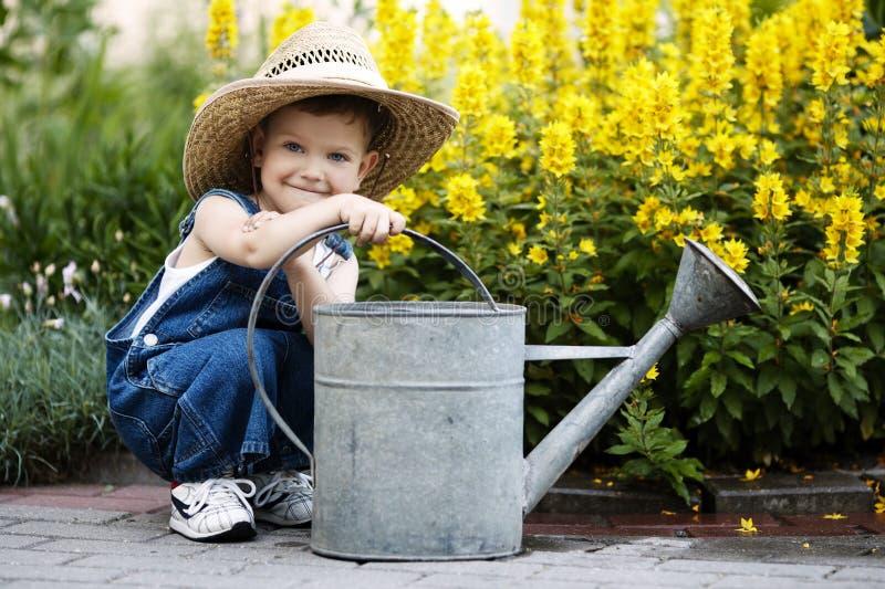 Rapaz pequeno com a lata molhando no parque do verão imagem de stock