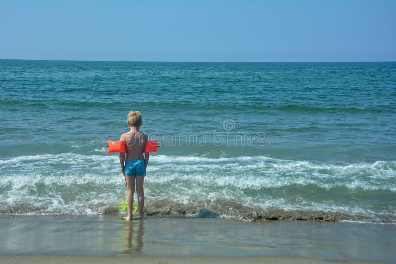 Rapaz pequeno com luvas da natação, suportes na praia imagem de stock royalty free