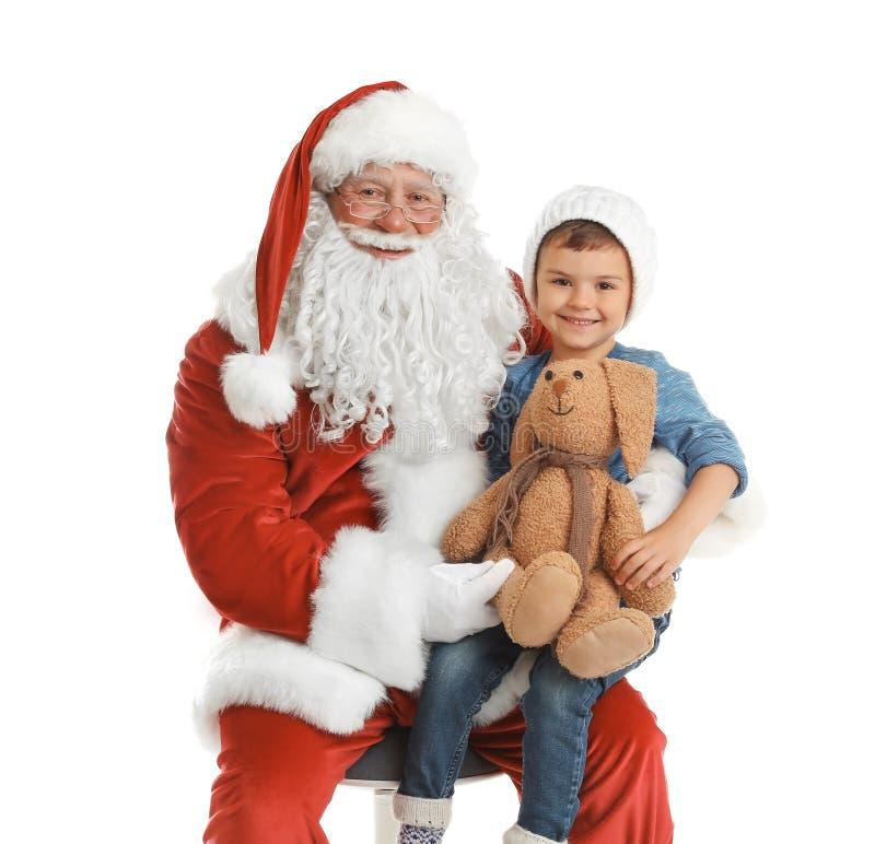 Rapaz pequeno com o coelho do brinquedo que senta-se em Santa Claus autêntica foto de stock royalty free
